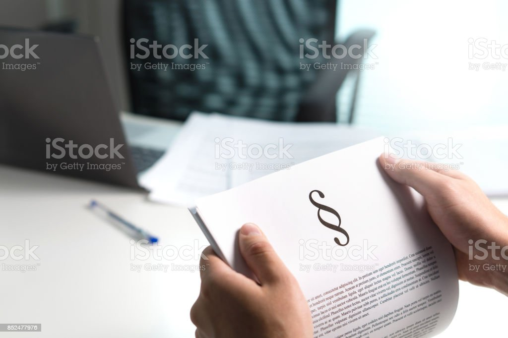 Man holding a legal document in hand with a section sign home. Lawyer holding law paper in office. stock photo