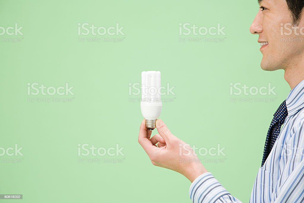 Homem segurando uma lâmpada foto de stock royalty-free