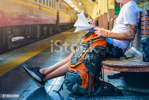 istock Man holding a map with backpack, camera and a smart phone in a train station 873902688