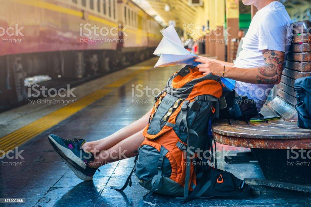 Mann im Besitz einer Karte mit Rucksack, Kamera und ein Smartphone in einem Bahnhof – Foto