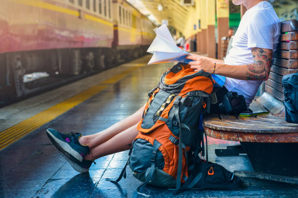 man holding a map with backpack, camera and a smart phone in a train station - saccopelista foto e immagini stock