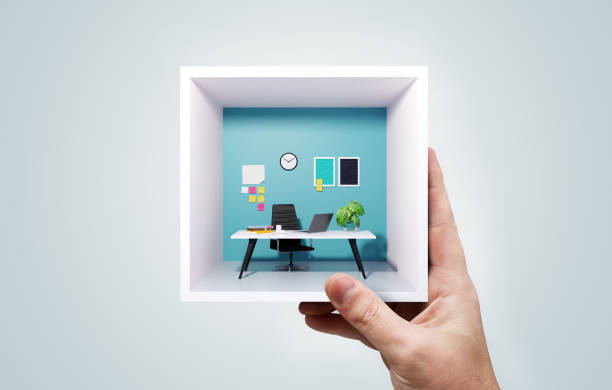 A Man Holding A Miniature Business Office Work Space stock photo