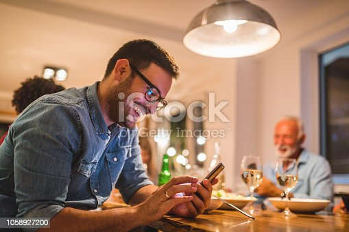 istock Man holding a mobile phone while dining with family 1058927200