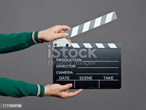 Man holding a movie clapperboard, studio shot