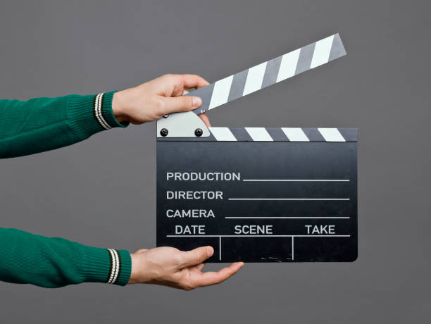 Man holding a movie clapperboard, studio shot stock photo