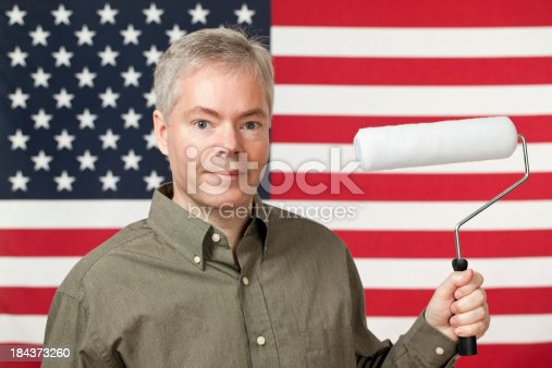 Man holding a paint roller standing in front of an American flag. Hey America! Let's paint this town.Please also see: