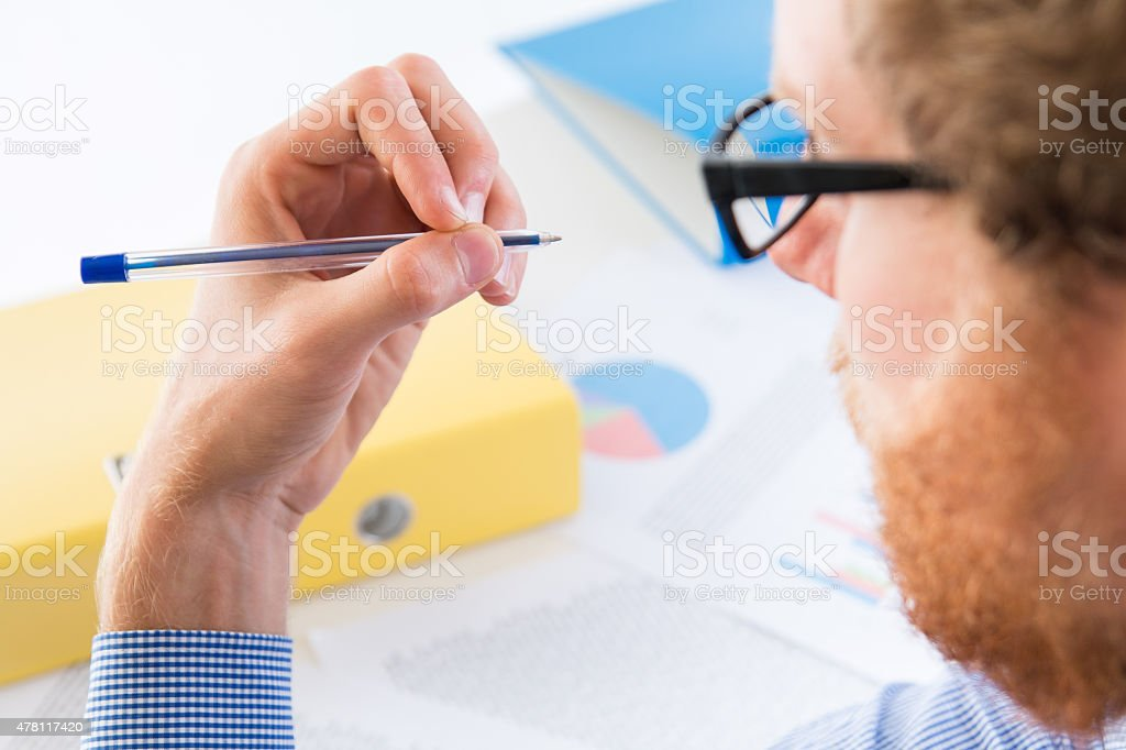 Man holding a pen with his left hand stock photo