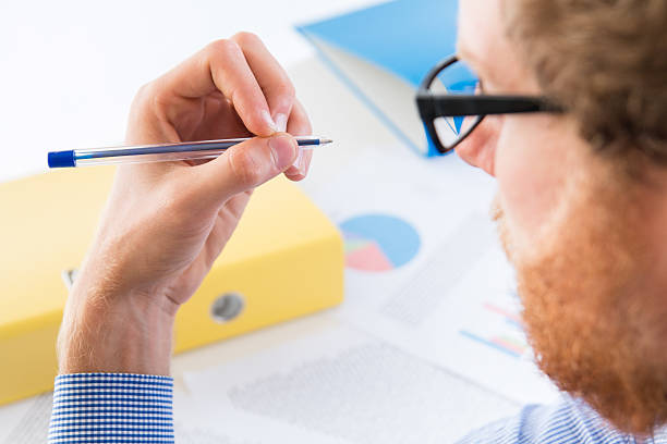 Man holding a pen with his left hand Man holding a pen with his left hand - office illiteracy stock pictures, royalty-free photos & images