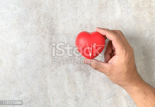 823097608istockphoto Man holding a red heart shape on marble table 1127210080