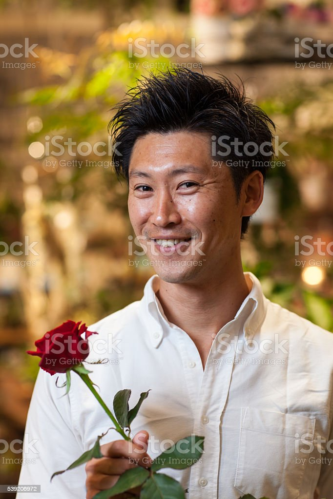 Man holding a rose in a flower shop