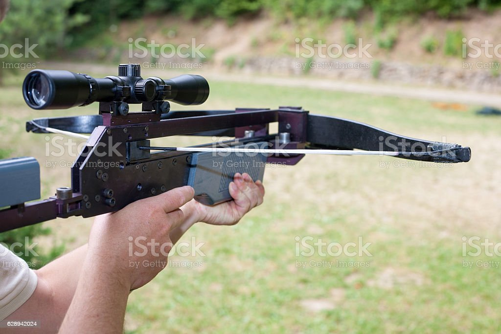 Man holding a scoped crossbow - Photo