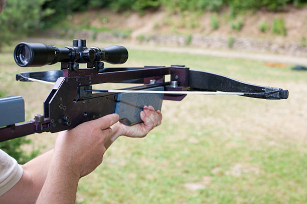 man holding a scoped crossbow - crossbow stock pictures, royalty-free photos & images