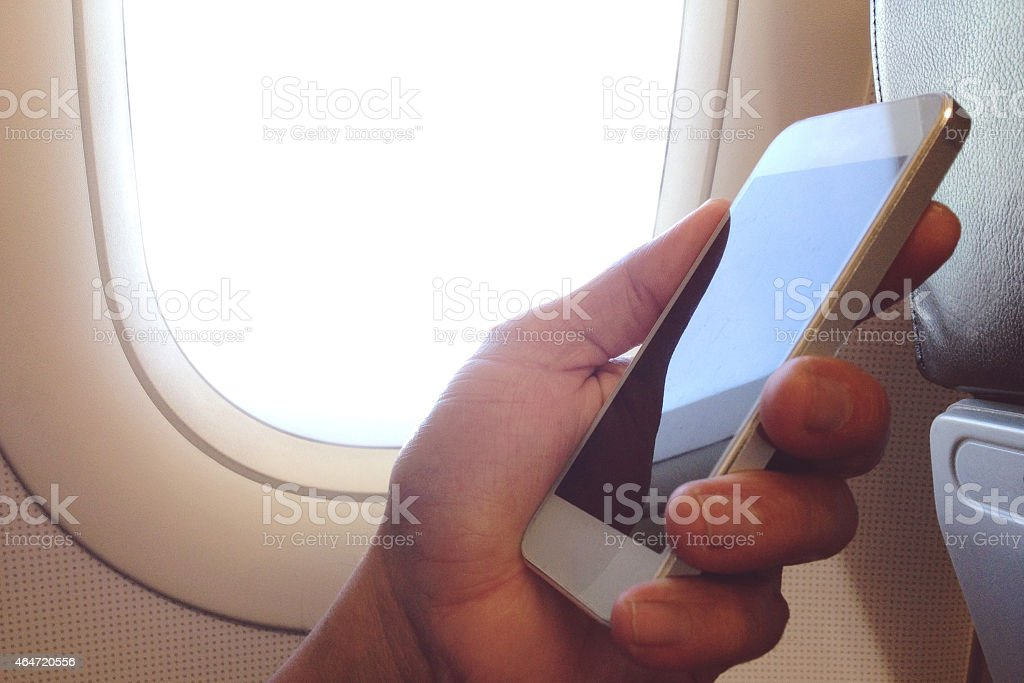 Man holding a smartphone while seated by an airplane window stock photo