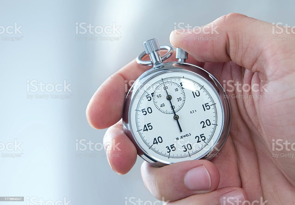 A man holding a stopwatch on his hand stock photo
