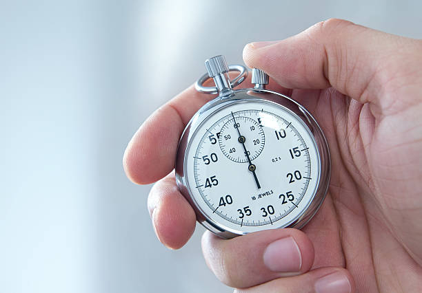 a man holding a stopwatch on his hand - stopwatch stockfoto's en -beelden