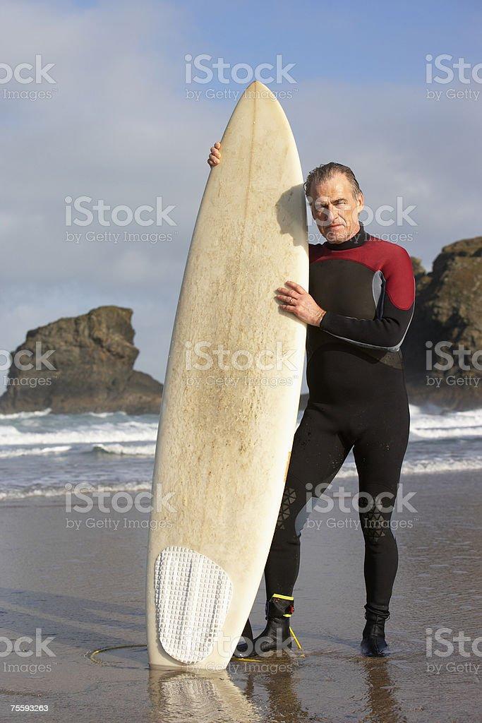 Homem segurando uma prancha de surf foto de stock royalty-free