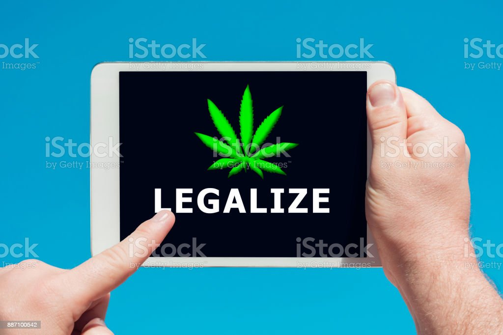 Man holding a tablet device showing a 'legalize marihuana' concept stock photo