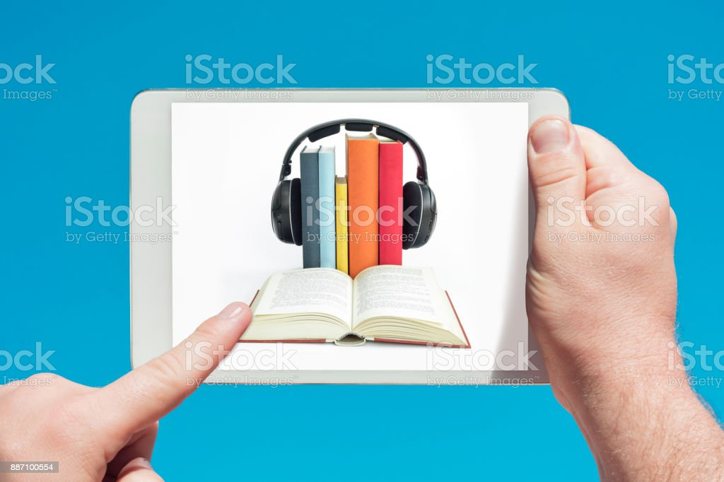 Man holding a tablet device showing audio books (e-book) concept stock photo