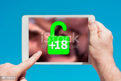 istock Man holding a tablet device showing lock icon allowing permission to people over 18 to watch adult content 887100576