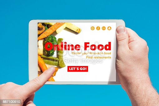 Man holding a tablet device visiting an online food website and touching the screen with a finger with blue sky in background.