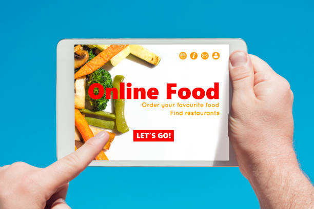 Man holding a tablet device visiting an online food website and touching the screen with a finger with blue sky in background stock photo
