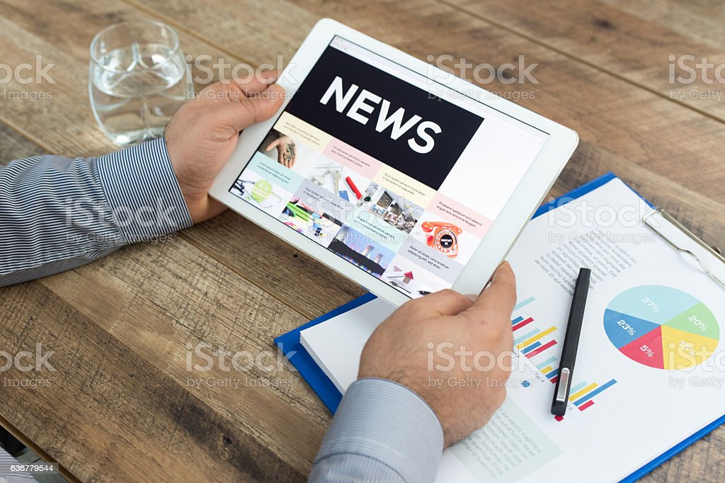 Man holding a tablet showing News concept stock photo