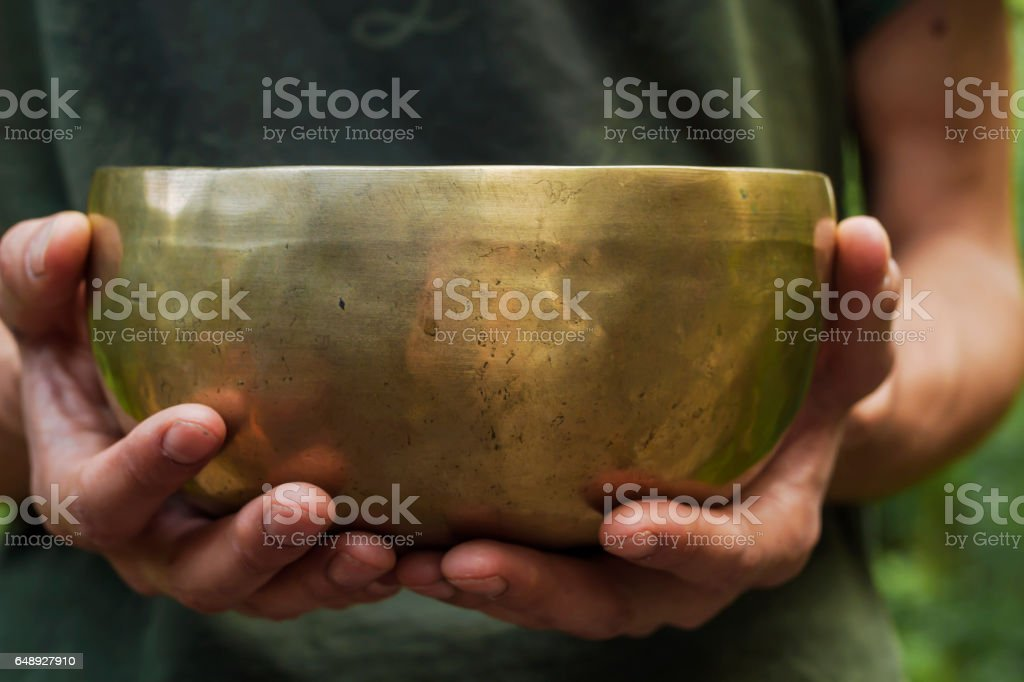 man holding a tibetan bowl stock photo