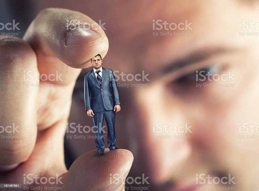 A man holding a tiny businessman between his fingers royalty-free stock photo