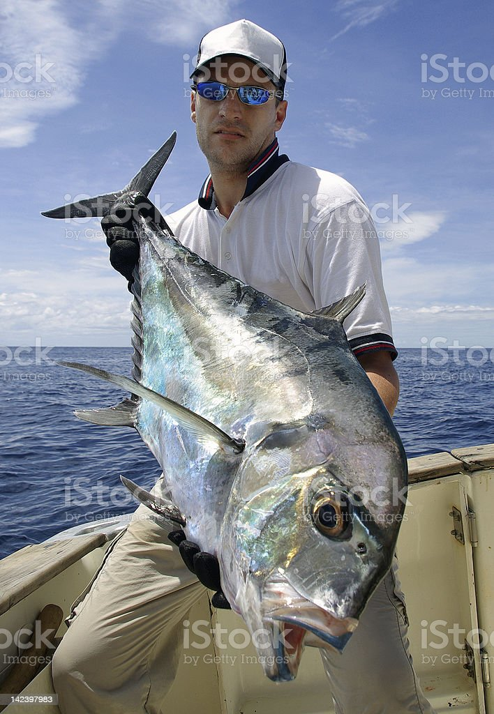 A man holding a Trevally Jack fish in a boat stock photo