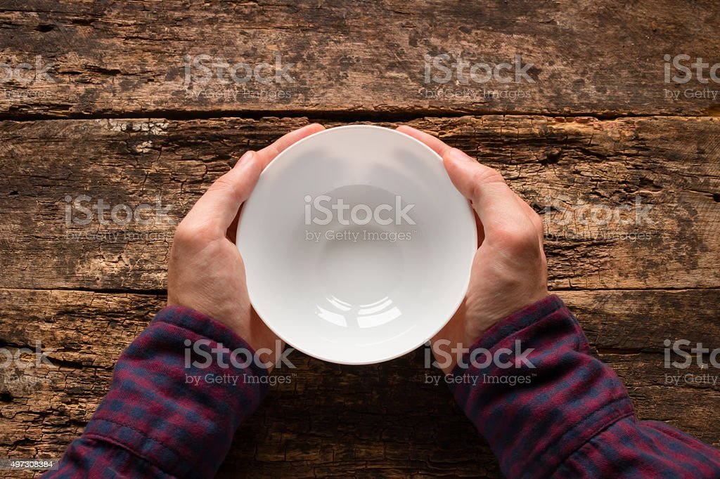man holding a white empty cup on a wooden background stock photo