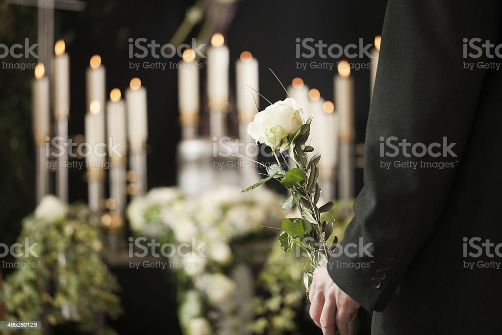 Man holding a white rose in front of urn at funeral stock photo