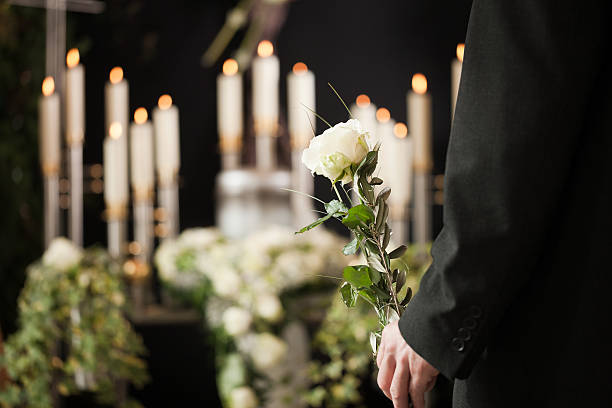 Man holding a white rose in front of urn at funeral Religion, death and dolor  - man at funeral with white rose mourning the dead mourning stock pictures, royalty-free photos & images