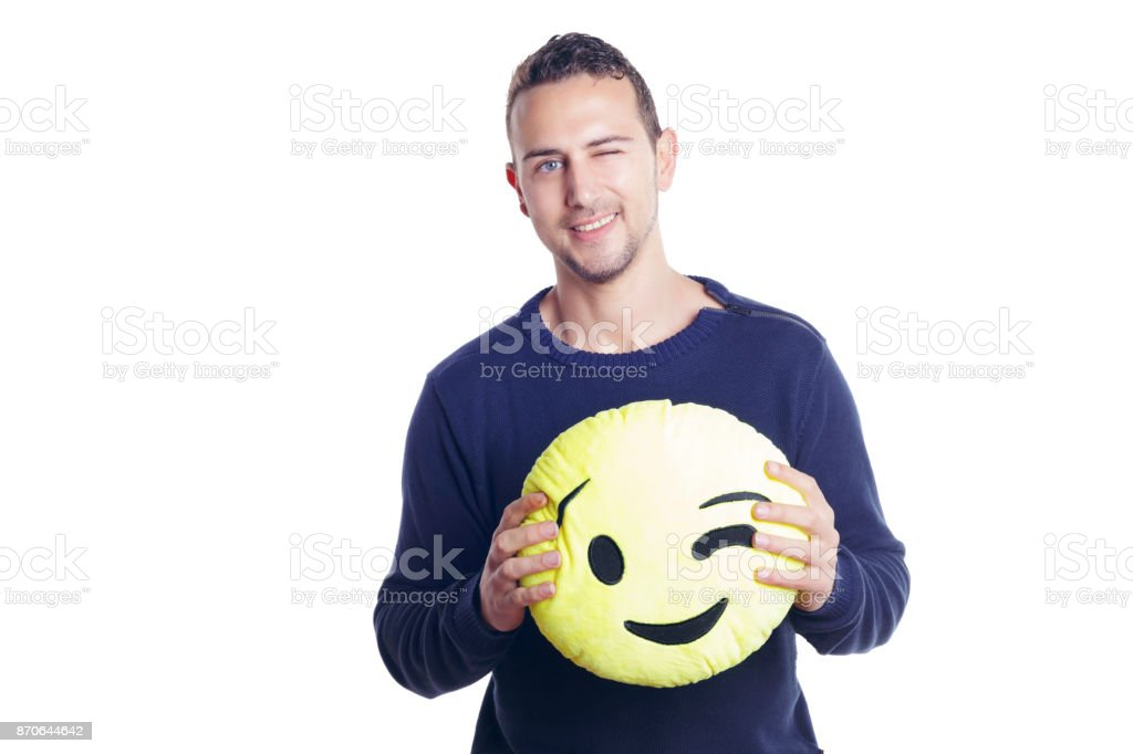 Man holding a winking emoji plush. stock photo