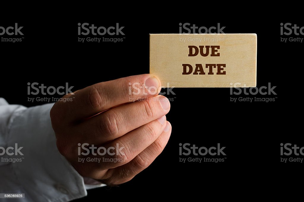 Man holding a wooden sign saying Due Date stock photo