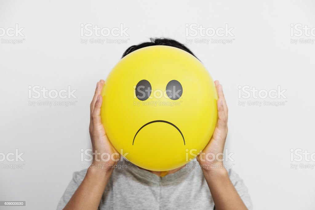 man holding a yellow balloon with sadly face emoticon stock photo