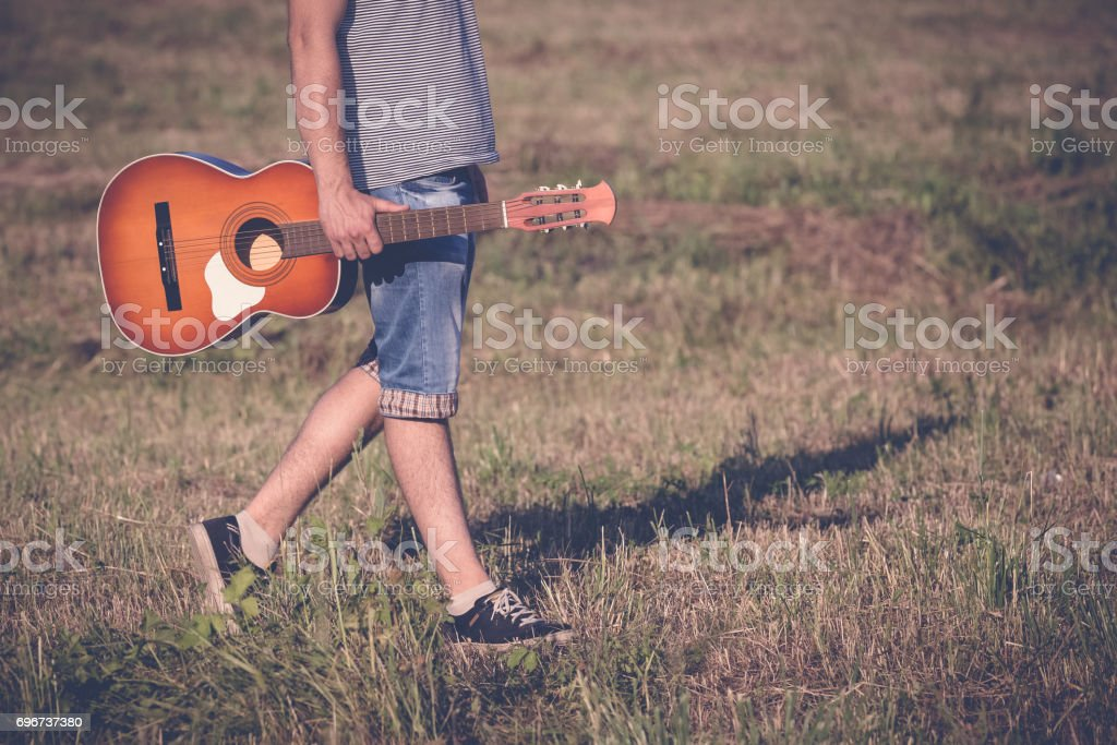 Man holding acoustic guitar and walking on the meadow. Music, instruments and lifestyle concepts. stock photo