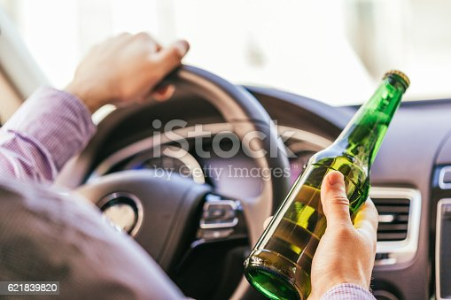 istock man holding alcohol while driving the car 621839820