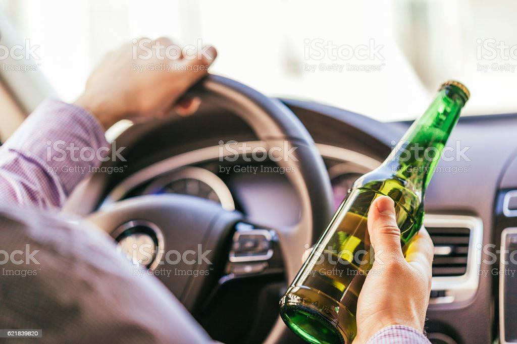 man holding alcohol while driving the car stock photo
