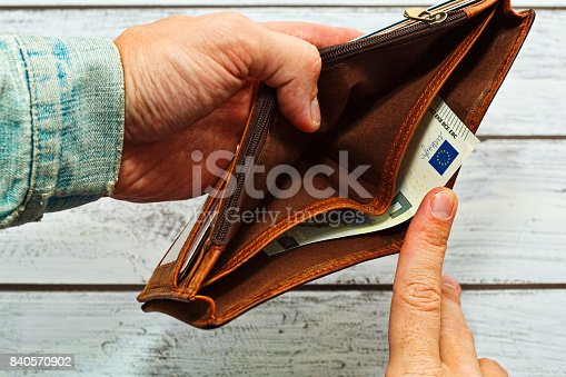 istock Man holding almost empty leather wallet 840570902