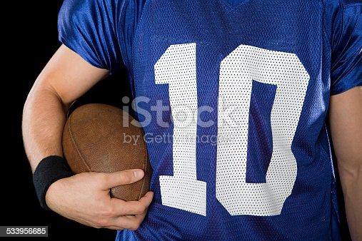 511849865istockphoto Man holding american football 533956685