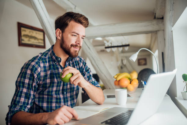 Man holding an apple and looking at laptop stock photo