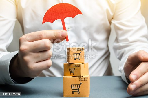 506662064istockphoto A man holding an umbrella above the boxes. Insurance of purchases and parcels, money back guarantee and non-damage to the goods upon shipment. Internet trade, commerce, market. Free trade zone. 1129922784