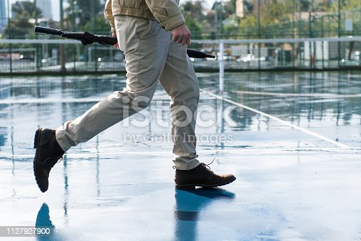 A man dressed and prepared for the gloomy weather walks across a puddle filled tennis court on his way to work.