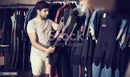 Adult european man holding and choosing suit for surfing in the shop