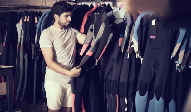 man holding and choosing suit for surfing in the shop Adult european man holding and choosing suit for surfing in the shop wetsuit stock pictures, royalty-free photos & images