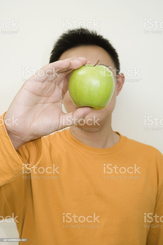 Man holding apple in front of face foto de stock libre de derechos
