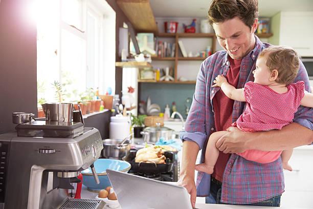 vater mit junger tochter mit laptop in der küche - hausmannskost stock-fotos und bilder