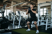 istock Man holding ball and doing squats. 1277242858