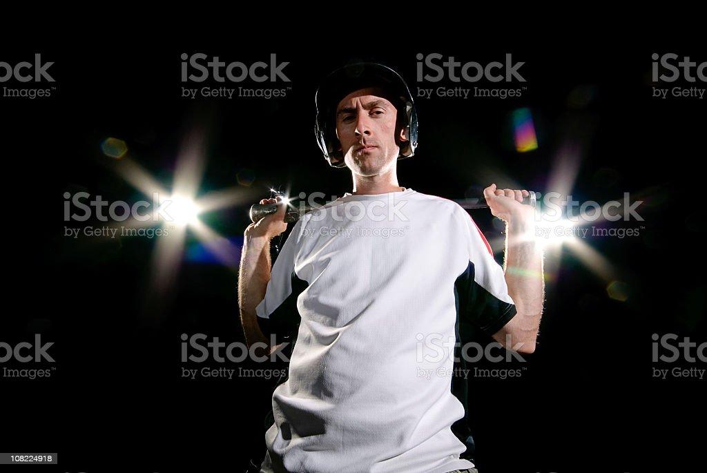 Man Holding Basball Bat Under Stadium Lights stock photo