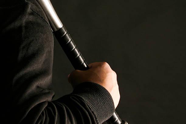 man holding baseball bat - baseball bat stock photos and pictures